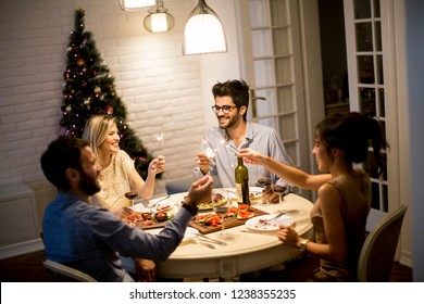 Young friends celebrating Christmas or New Year eve at home