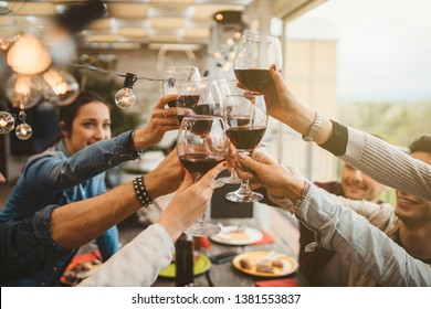 Young friends celebrating at dinner at sunset - Detail of hands while toasting with glasses of wine - Happy people at a terrace party after the harvest before sunset - Concept of friendship