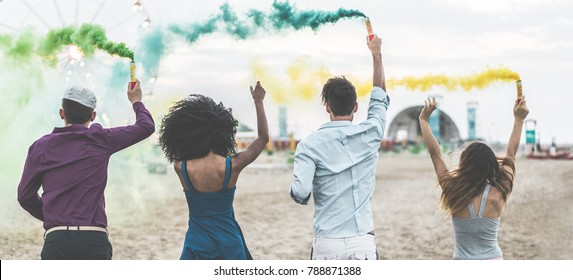 Young friends celebrating at party festival with smoke bombs on the beach - Happy people having fun in summer vacation - Friendship, youth lifestyle and fest concept - Main focus on center guys