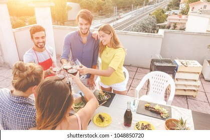 Young friends cheering with red wine at rooftop barbecue party - Happy people doing bbq dinner outdoor with city view in background - Focus on glasses - Food, fun and friendship concept