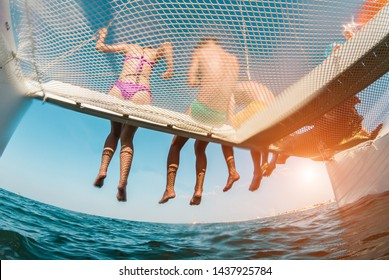Young friends chilling in catamaran boat - Group of people making tour ocean trip - Travel, summer, friendship, tropical concept - Focus on guys legs - Fisheye lens distorsion