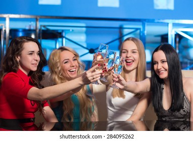 Young friends clanging glasses with sparkling wine. Blonde, brunette and chestnut girls in clubbing wearing satisfied by their happy evening in nightclub.
