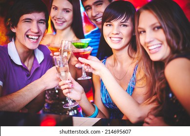 Young friends with cocktails looking at camera at party with focus on happy girl and guy