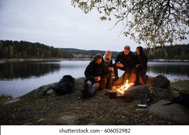 Young Friends With Coffee Cups Sitting Near Campfire