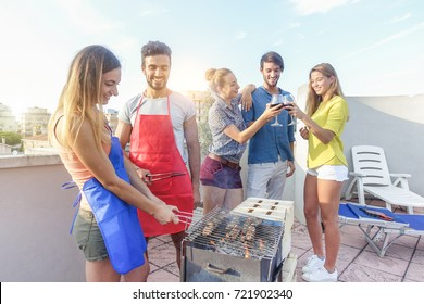 Young friends cooking meat at dinner barbecue party and drinking red wine - Happy people grilling and having fun at bbq meal at sunset - Food, fun and friendship concept - Warm filter