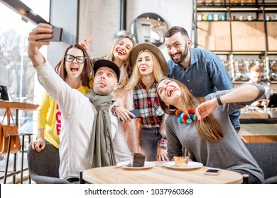 Young friends dressed casually having fun making self portrait together in the cafe