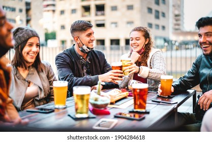Young friends drinking beer pint with open face mask - New normal lifestyle concept with milenials having fun together talking at outside brewery bar - Warm filter with focus on left central guy