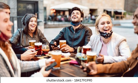 Young friends drinking beer wearing face mask - New normal lifestyle concept with people having fun together talking on happy hour at outside brewery bar - Bright warm filter with focus on central guy - Shutterstock ID 1841791990