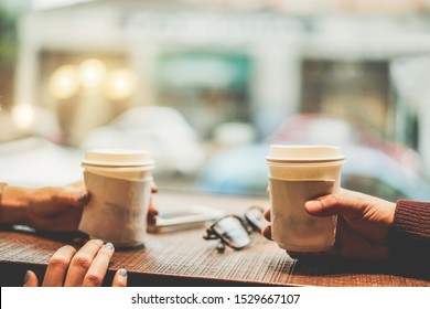 Young friends drinking coffee in paper recycled cup - People having a break sitting in bar restaurant toasting a cappuccino - Winter, fall, city trends and lifestyle concept - Focus on right hand