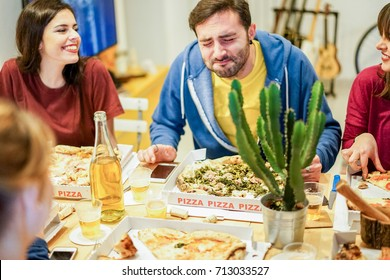 Young friends eating italian pizza take away at home - Happy students having fun at dinner in hostel - Friendship and youth concept - Focus on man's pizza paper box - Warm filter