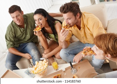 Young friends eating pizza at home, having fun.