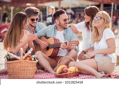 Young friends enjoying a beach party with music and drinks.Young man playing guitar with his friends.