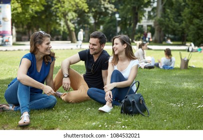 Young friends enjoying spring in park, sitting on grass, talking.