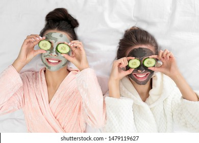 Young friends with facial masks having fun on bed at pamper party, top view