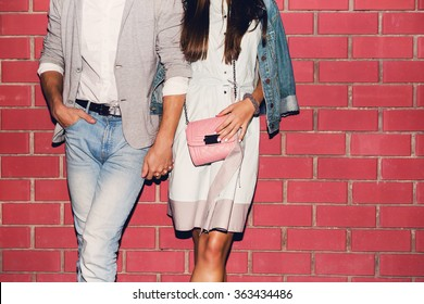 Young friends funny guys active people have fun together woman and man, girl and guy summer urban casual style. Pink brick wall, spring  outfit.