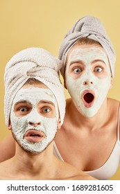 Young friends guy and girl with funny expressive emotions, towel on head and face mask isolated on a yellow background, skin care concept