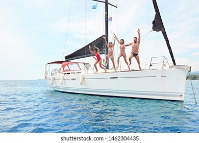 young friends hanging out, having fun and enjoying summer days jumping from sailing boat in sea.