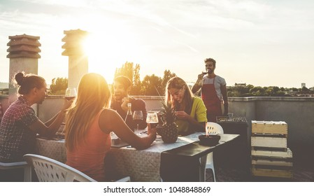 Young friends having barbecue party at sunset on penthouse patio - Happy people doing bbq dinner outdoor cooking meat and drinking wine - Focus on right woman - Food, fun and friendship concept