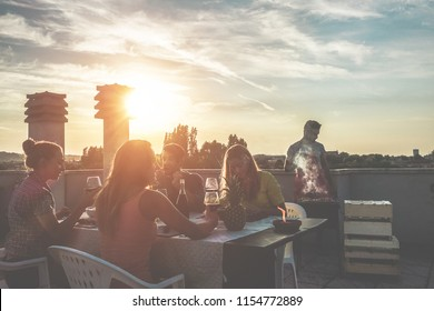 Young friends having barbecue party at sunset on penthouse terrace - Happy people doing bbq dinner outdoor cooking meat and drinking wine - Focus right woman face - Food, fun and friendship concept