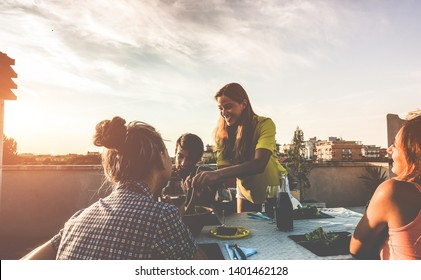 Young friends having barbecue party at sunset on terrace patio - Happy people doing bbq dinner outdoor eating and drinking wine - Focus on right woman face - Food, fun and friendship concept