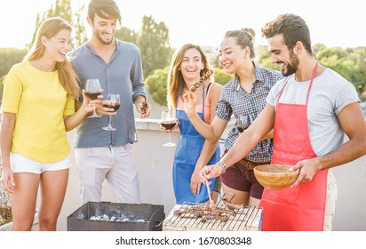 Young friends having barbecue party at sunset on house patio - Happy people doing bbq dinner outdoor cooking meat and drinking wine - Main focus on right man face - Food, fun and friendship concept