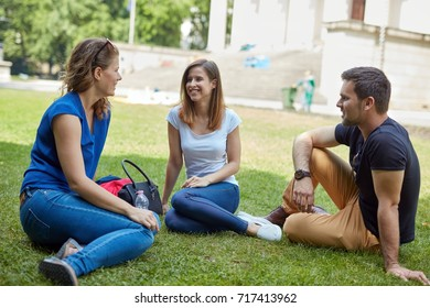 Young friends having a break, sitting in park, talking in a sunny day.