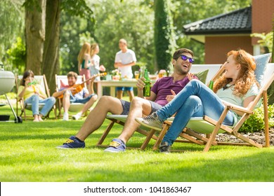Young friends having fun at backyard barbecue party, drinking beer, talking and playing guitar on hot summer day, focus on the couple laughing sitting on deck chairs
