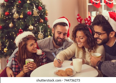 Young friends having fun at Christmas day, writing a letter to Santa Claus. Focus on the girl writing