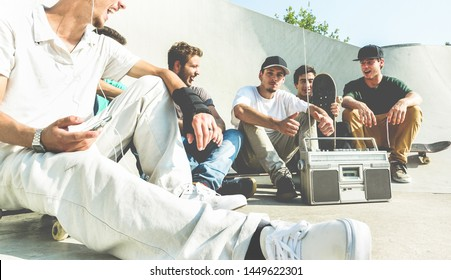 Young friends having fun at city skate park at sunset - Happy skaters laughing and listening music with vintage stereo - Extreme sport, friendship, youth, lifestyle concept - Focus on right man face