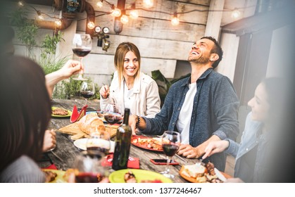 Young friends having fun drinking red wine on balcony at house dinner party - Happy people eating bbq food at fancy alternative restaurant together - Dining lifestyle concept on desaturated filter - Shutterstock ID 1377246467