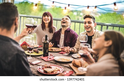 Young friends having fun drinking red wine at balcony penthouse dinner party - Happy people eating bbq food at fancy alternative restaurant together - Dinning lifestyle concept on warm vintage filter