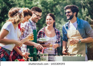 Young friends having fun grilling meat enjoying barbecue party.