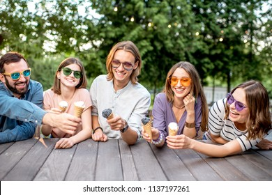 Young friends having fun with ice cream sitting together outdoors in the park