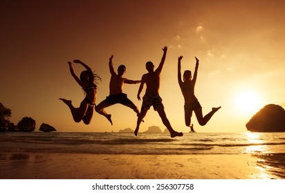 Young friends having fun on the beach and jumping against a backdrop of a sunset over the sea. Phranang beach, Krabi province, Thailand