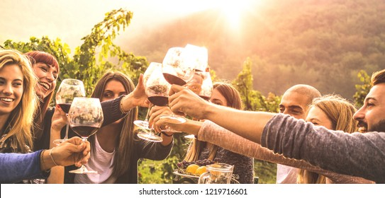 Young friends having fun outdoor - Happy people enjoying harvest time together at farm house winery countryside - Youth friendship concept - Hand toasting red wine at pic nic in vineyard before sunset