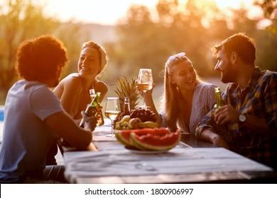 Junge Freunde, die sich im Freien amüsieren, reden und lachen, am Abend genießen.