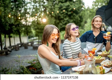 Young friends having fun together with snacks and drinks during the evening light outdoors in the park cafe
