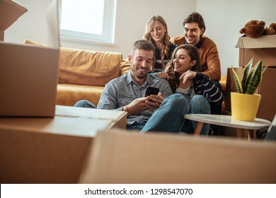 Young friends having fun and using phone indoors