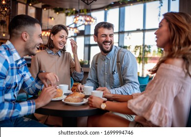 Young friends having a great time in restaurant. Group of young people sitting in a coffee shop ,drinking coffee.