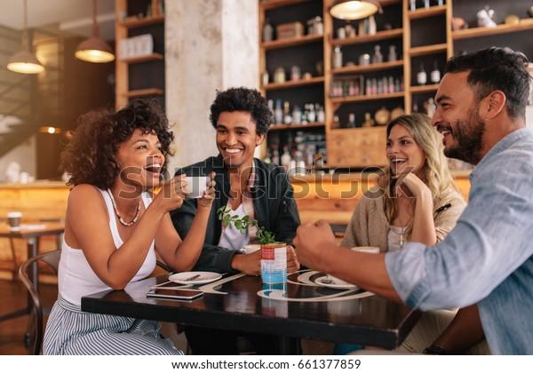 Молодые друзья, отлично проводившие время в ресторане. Многорасовая группа молодых людей сидит в кафе и улыбается.