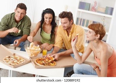 Young friends having party at home, eating pizza and chips, smiling.