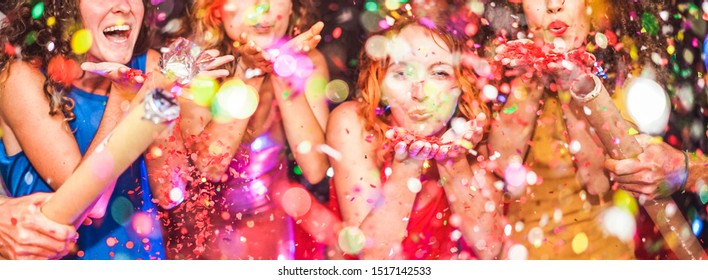 Young friends having party throwing confetti - Young people celebrating on weekend night - Entertainment, fun, new year's eve, nightlife, holidays, concept - Focus on red hair girl hands