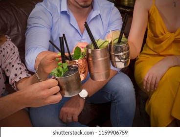 Young friends holding alcoholic drink glasses detail in a bar pub restaurant