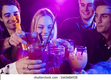 Young friends holding cocktails in nightclub
