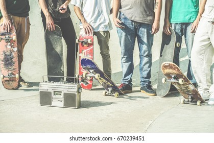 Young friends holding skateboards in hands outdoor on city skate park  - Teen friends having fun skating and listening music outside - Extreme sport,friendship,youth concept - Contrast retro filter