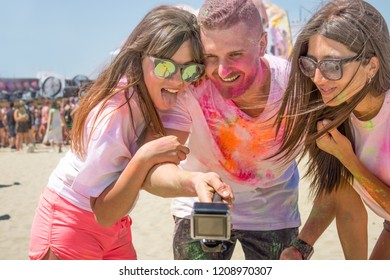 young friends at holi color festival smiling having fun party taking selfie photo. concept of friendship and party live events freedom and fun