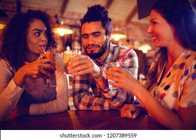 Young friends interacting with each other having drinks in pub