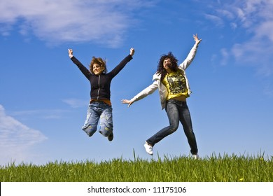 Young friends jumping on green meadow
