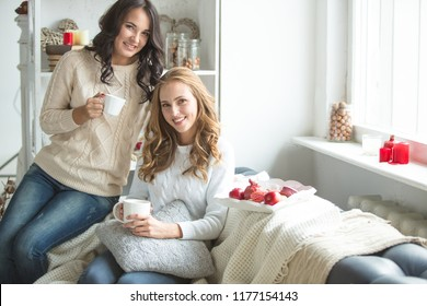 Young friends in knitted things are sitting on the sofa. Girls enjoy communication