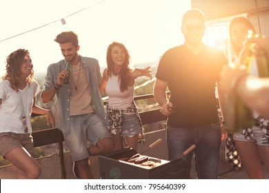 Young friends making barbecue, drinking beer and enjoying hot summer days having fun on a rooftop party. Focus on the girl in the middle